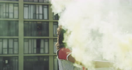 on camera : Front view close up of a hip young mixed race woman standing and holding smoke grenade on an urban rooftop, looking to camera, with a building in the background