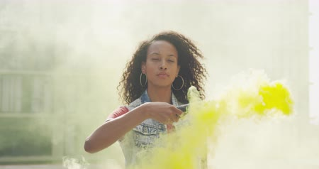 granada : Front view close up of a hip young mixed race woman standing and holding smoke grenade on an urban rooftop, eyes closed, than looking to camera, with a building in the background