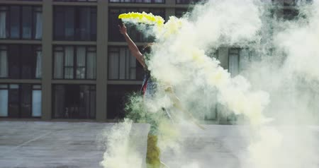 granada : Side view of a hip young mixed race woman walking and using smoke grenade on an urban rooftop, with a building in the background