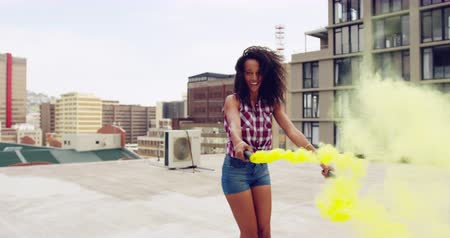 granaat : Front view of a hip young mixed race woman smiling, turning round and holding two smoke grenades on an urban rooftop, with buildings in the background