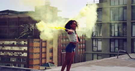 granaat : Back view of a hip young mixed race woman walking and using smoke grenade on an urban rooftop, with buildings in the background Stockvideo