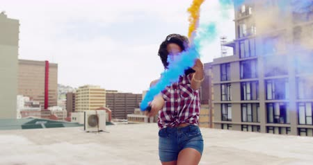 granada : Front view of a hip young mixed race woman walking and holding two smoke grenades on an urban rooftop, with buildings in the background Vídeos