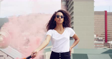 granada : Side view close up of a hip young mixed race woman walking and using smoke grenade on an urban rooftop with buildings in the background