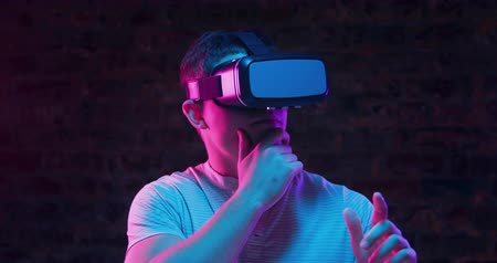 simulace : Front view close up of a young Caucasian man wearing a VR headset and looking around, with one hand to his chin an the other gesturing in front of him with pointed finger, lit with pink and blue light on a black background