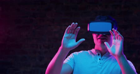 avoiding : Front view close up of a young Caucasian man wearing a VR headset, smiling and looking around and moving, with both hands raised in front of him as if avoiding things, lit with pink and blue light on a black background Stock Footage