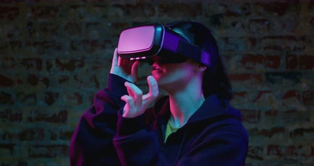 悪 : Side view close up of a young Caucasian woman wearing a VR headset, smiling and looking around, with one hand raised and gesturing as if swiping, lit with pink light against a brick wall background