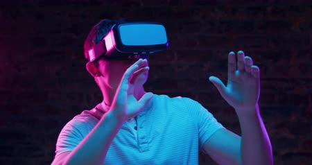 kruk : Front view close up of a young Caucasian man wearing a VR headset, laughing, looking around and moving, with both hands raised in front of him as if avoiding things, lit with pink and blue light on a black background
