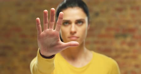 идентификация : Front view close up of a young Caucasian woman wearing a yellow top with arm raised and hand out in front of her, with palm facing camera, touching