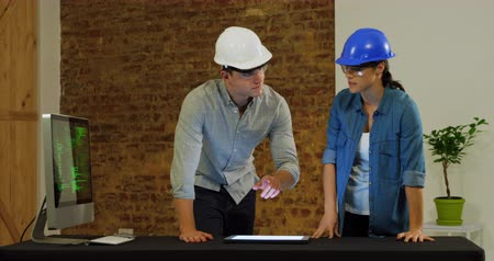 on site research : Front view close up of a young Caucasian man and woman wearing protective safety glasses and hard hats in discussion standing behind a table and looking at a tablet computer and a monitor displaying data