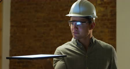 on site research : Front view close up of a young Caucasian man wearing protective safety glasses and a hard hat holding a tablet computer flat on his hand, looking at it and using the touchscreen