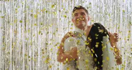 festividades : Close up of a happy young Caucasian bride and groom in traditional formal clothes dancing together closely under falling golden confetti and embracing in front of a curtain of shiny silver fringes, backlit by a spotlight Vídeos