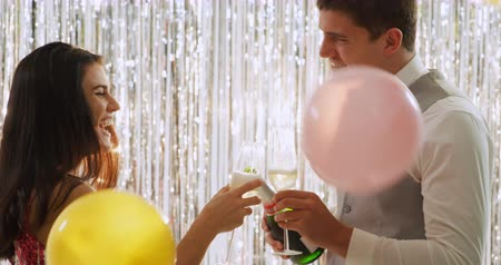 festividades : Side view close up of a smartly dressed young Caucasian couple pouring glasses of champagne, drinking a toast and laughing at a party, with balloons falling, in front of a curtain of shiny silver fringes