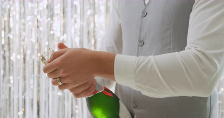 festividades : Side view mid section of a young Caucasian man wearing a white shirt and grey waistcoat opening a bottle of champagne in front of a curtain of shiny silver fringes