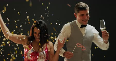 companionship : Front view close up of a smartly dressed smiling young Caucasian couple holding glasses of champagne, dancing under falling confetti and balloons, and posing for a picture with party photo props at a party, against a black background
