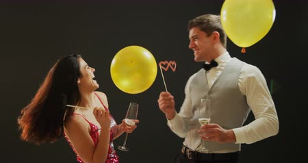 festividades : Front view close up of a smartly dressed smiling young Caucasian couple drinking glasses of champagne, dancing under falling balloons and posing for a picture with party photo props at a party, against a black background Vídeos