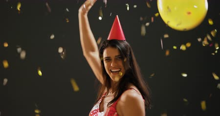 festividades : Front view close up of a happy young Caucasian woman with long dark hair wearing an evening dress and a paper party hat, dancing under falling confetti at a party