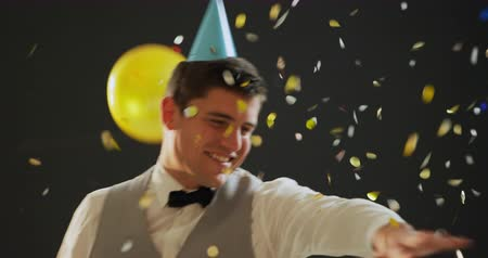 festividades : Front view close up of a happy young Caucasian man wearing a bow tie, waistcoat and a paper party hat, dancing under falling confetti and balloons at a party, on a dark background
