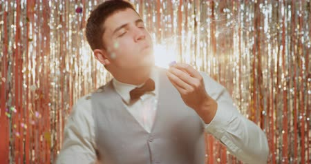festividades : Front view close up of a happy young Caucasian man wearing a bow tie and a waistcoat having fun dancing and blowing bubbles in front of a curtain of shiny silver fringes, backlit by a spotlight