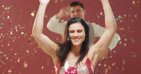 festividades : Front view close up of a happy young Caucasian woman wearing an evening dress blowing golden confetti from her hands at the camera and dancing under falling confetti at a party, a young Caucasian man dancing behind her, against a pink background