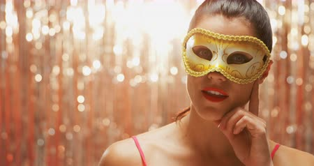 festividades : Front view close up of a happy young Caucasian woman wearing a carnival mask, touching her chin, smiling to camera in front of a curtain of shiny silver fringes, backlit by a spotlight Vídeos