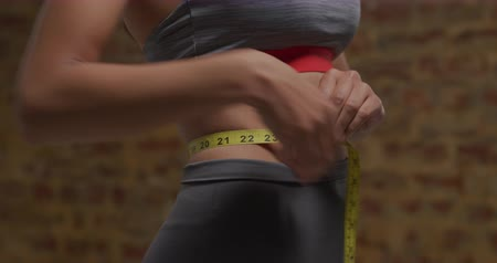 measure tape : Front view mid section of a young Caucasian woman wearing sports clothes measuring her waist with a yellow measuring tape Stock Footage