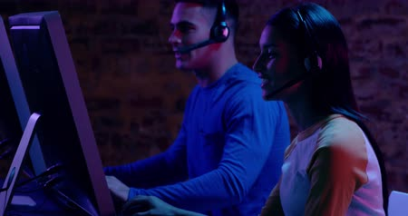 mouse de computadora : Side view close up of a young mixed race woman and a Caucasian man sitting beside each other working at computers in a darkly lit workspace Archivo de Video