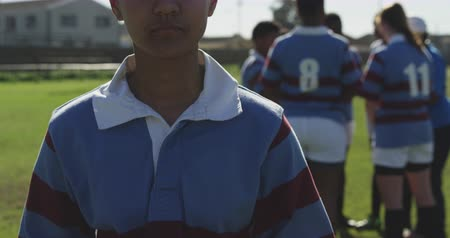 rugby shirt : Portrait of a young adult mixed race female rugby player standing on a rugby pitch holding a rugby ball in her hands looking to camera and smiling, with her teammates talking together in the background
