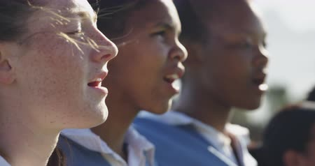 rugby shirt : Side view close up of a team of a young adult multi-ethnic female rugby players standing in a row on a rugby field singing in preparation for a rugby match