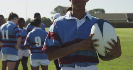 rugby shirt : Portrait of a young adult mixed race female rugby player standing on a rugby pitch holding a rugby ball, throwing it in the air and catching it, looking to camera and smiling, with her teammates talking together in the background