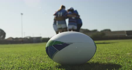 amontoado : Close up of rugby ball on a rugby pitch with a group of female rugby players in a huddle in the background
