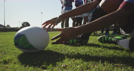 cipőfűző : Low angle low section of a young adult mixed race female rugby player sitting on a rugby pitch and tying her boot with the ball beside her, picking up the ball and walking with it to her teammates, talking in the background