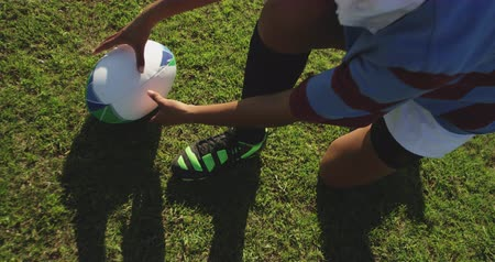 cipőfűző : High angle low section of a young adult mixed race female rugby player sitting on a rugby pitch and tying her boot with the ball beside her, picking up the ball and walking with it to her teammates, talking in the background