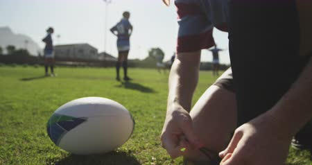 cipőfűző : Close up of a young adult mixed race female rugby player kneeling and tying her boot on a rugby pitch, with the ball beside her and teammates in the background