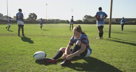 cipőfűző : Front view close up of a young adult Caucasian rugby player sitting and tying her boot on a rugby pitch and picking up the ball beside her, with teammates in the background Stock mozgókép