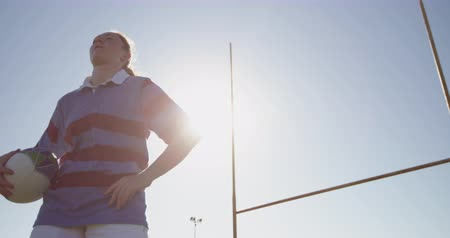 rugby shirt : Front view low angle of a young adult Caucasian female rugby player standing on a rugby pitch looking away with her hand on her hip, holding a rugby ball with the goalposts behind her, backlit Stock Footage