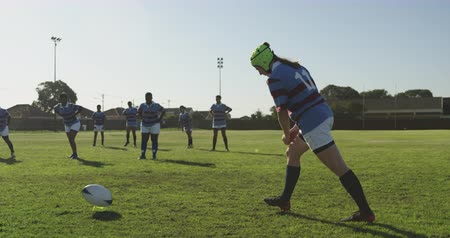rugby shirt : Side view of a young adult Caucasian female rugby player making a place kick during a rugby match, with a group of young adult multi-ethnic female players in the background