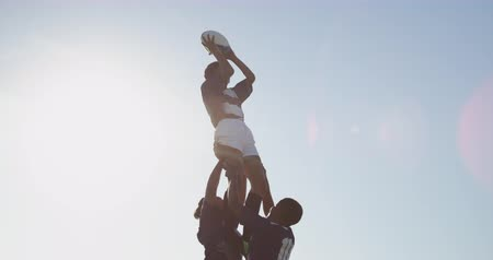 alcançando : Side view of a young adult mixed race female rugby player being lifted by two teammates to catch the ball and throwing it to a teammate during a rugby match