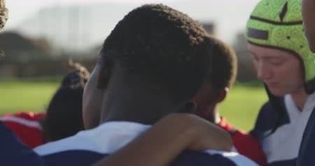 amontoado : Rear view of a team of young adult multi-ethnic female rugby players standing on a rugby field in a huddle having a moment of silent thought in preparation for a rugby match