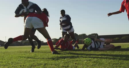rugby shirt : Front view of a group of young adult multi-ethnic female rugby players running on the pitch during a rugby match, and one player bringing another down with a tackle
