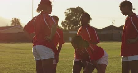 amontoado : Side view of a team of young adult multi-ethnic female rugby players standing in a huddle on a rugby pitch relaxing after a rugby match