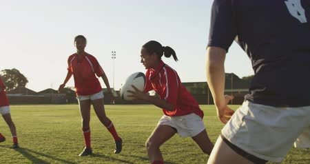 opponent : Side view close up of a group of young adult multi-ethnic female rugby players running on the pitch during a rugby match, and the player with the ball dodging attacks from the other team Stock Footage