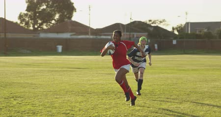 rúgbi : Front view of a young adult mxed race female rugby player running on the pitch holding the ball with a young adult Caucasian female player running after her during a rugby match, backlit