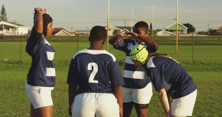 amontoado : Side view of a group of young adult multi-ethnic female rugby players relaxing on the pitch after a match with one Caucasian female player wearing a headguard Stock Footage