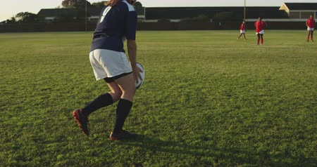opponent : Rear view of a young adult Caucasian female rugby player wearing a headguard making a drop kick during a rugby match, with other players in the background Stock Footage
