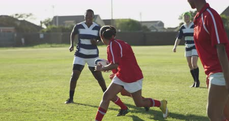 rubín : Side view of a group of young adult multi-ethnic female rugby players running on the pitch during a rugby match, one player passing the ball