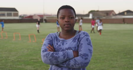 s rukama zkříženýma : Portrait close up of a young adult African American female rugby player standing on a sports field looking to camera, with her teammates training in the background