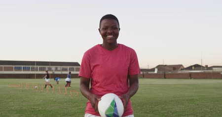 rugby ball : Portrait of a young adult African American female rugby player standing on a sports field holding a rugby ball, throwing and catching it in her hands and looking to camera smiling, with her teammates training in the background