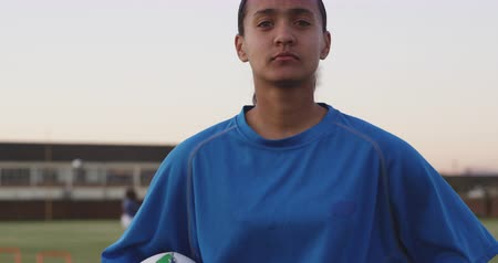 rúgbi : Portrait close up of a young adult mixed race female rugby player standing on a sports field looking to camera holding a rugby ball, with her teammates training in the background Vídeos