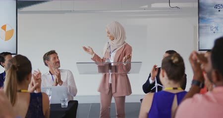 delegate : Front view close up of a young Asian businesswoman wearing a hijab standing on a stage at a lectern being applauded by the audience at a business conference. The backs of the seated audience are seen in the foreground Stock Footage