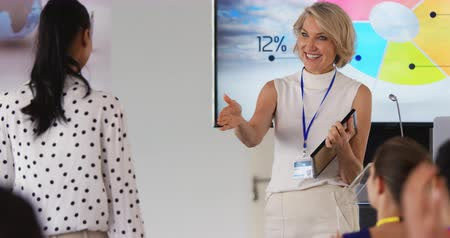 convidativo : Front view of a middle aged Caucasian businesswoman with blonde hair inviting a young woman to the stage where she shakes her hand and presents her with an award at a business conference. On the stage behind her screens are displaying information, the bac